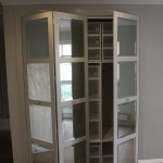 Built in wardrobe with folding doors and bevelled mirror inserts.